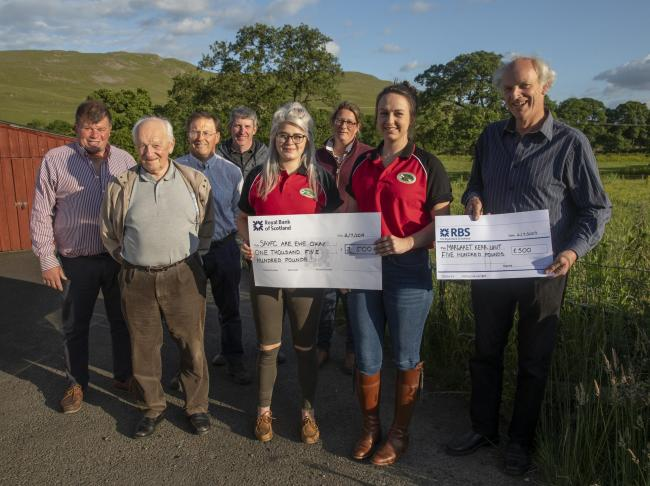 Committee members Jim Currie, Hayden Cameron, Jimmy Smellie, David Wallace, Becky Graham and Robert Barr presented the cheque for £1,500 to Abbie Barbour and Morgaine McKay from Peeblesshire Junior Agricultural Club. Photo: Linda Dick