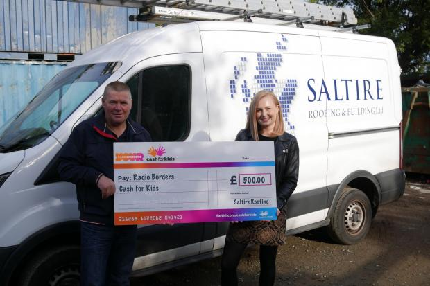 Steven McIntosh giving his company's Cah For Kids Mission Christmas donation to Radio Borders' regional charity manager, Emma Kemp. Photo: Radio Borders
