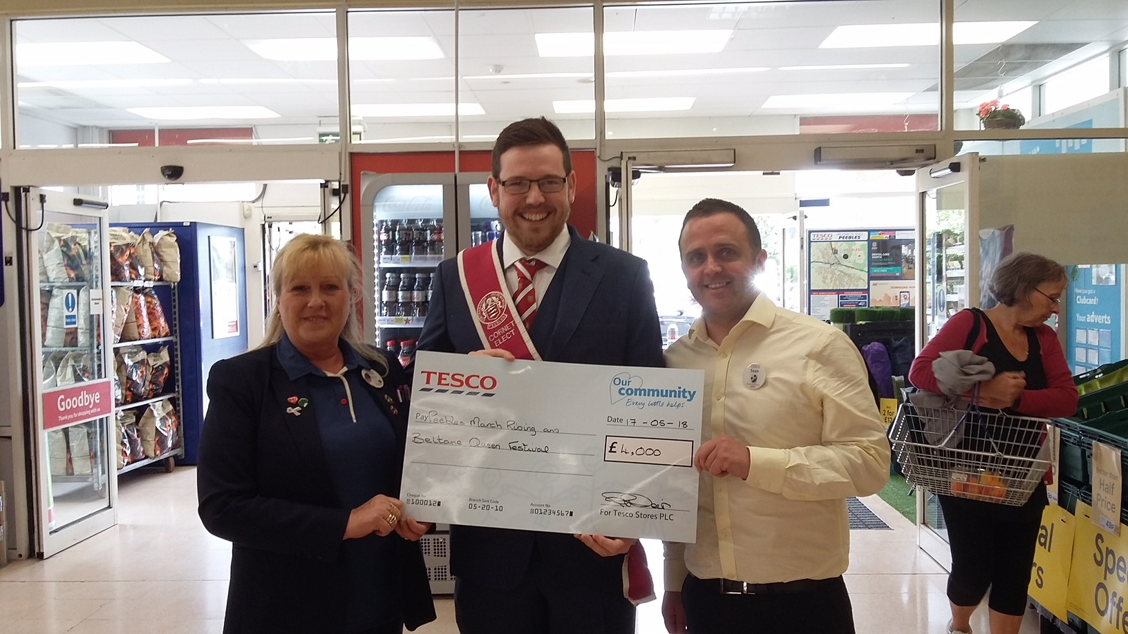Cornet-Elect Gregor McGrath collects the cheque from Tesco Community Chamption Pauline Weir.