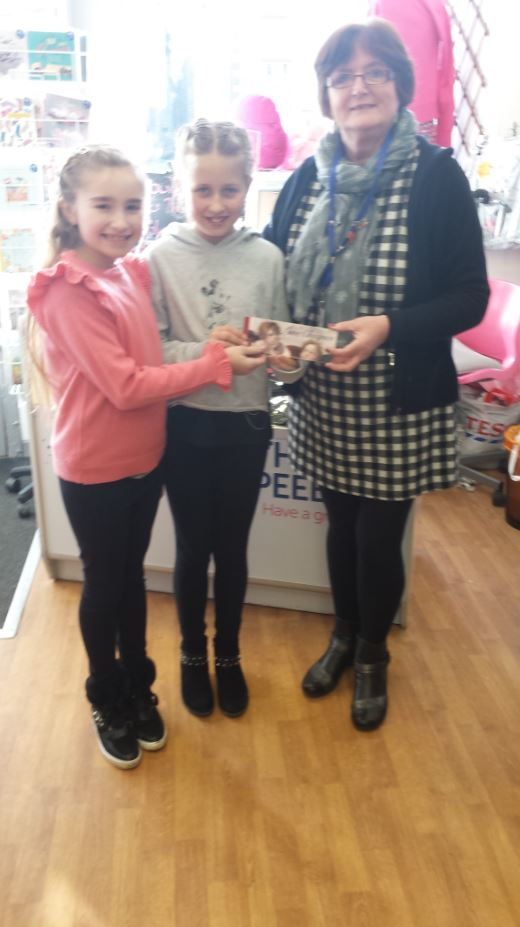 Ruby and Taylor hand their takings over to Dawn from Cancer Research in Peebles